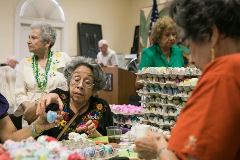 Angelica Teneyuca (center) reaches for an egg to fill with confetti while her twin sister Angelina De Peña (right) completes her own cascarón.