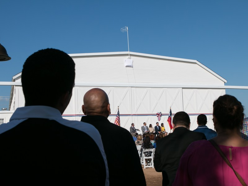 A large crowd stands in the shade for the grand opening of Hangar 9.