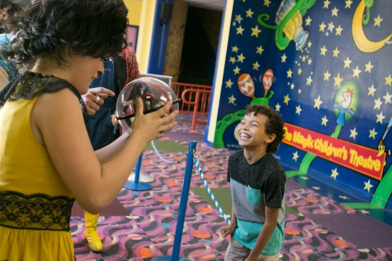 """Alexander, 7, bursts into laughter upon showing Magik Theatre actress Jovi Lee his puzzle game after the sensory-friendly performance of """"The Three Javelinas."""""""