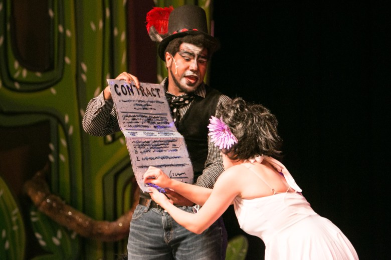 """(From left) Magic Theatre actor Venny Mortimer asks Magik Theatre actress Jovi Lee to sign a contract in the sensory-friendly performance of """"The Three Javelinas."""""""