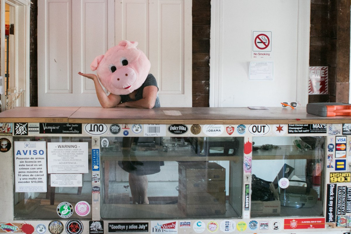 Anet Alaniz poses in her pig costume behind the bar area of the new Pig Liquors location.