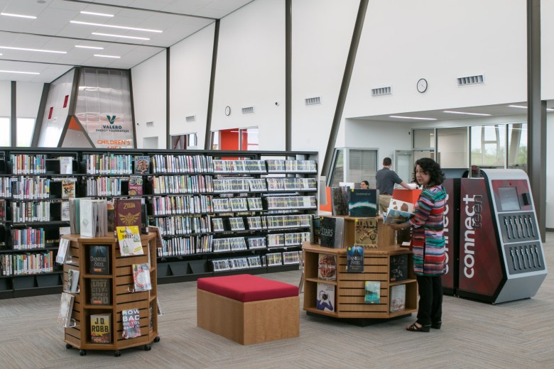 People meander through the aisles and displays of Schaefer Branch Library.
