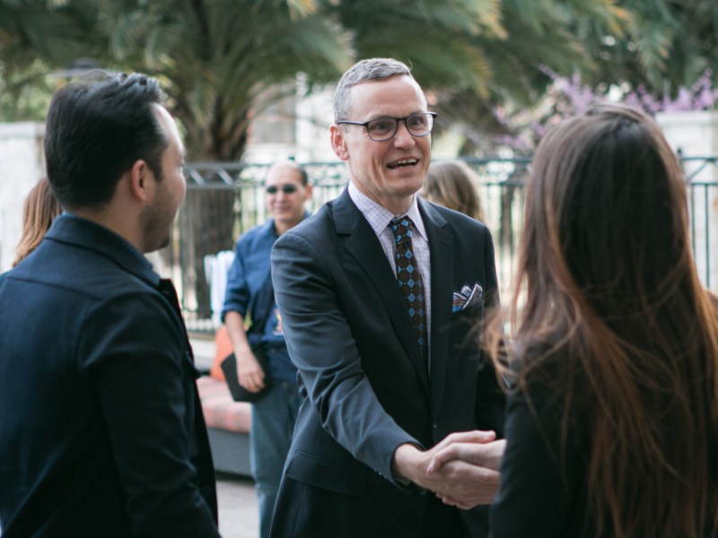Robert Amerman shakes hands with guests at the press conference.