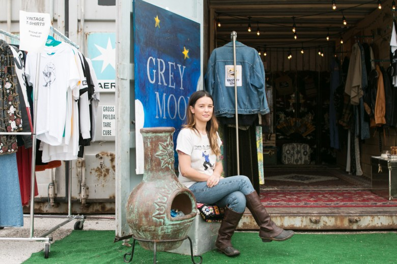 Co-owner of Grey Moon Vintage Natalie Medina sits outside of the company's storage container retail space located in a parking lot at 2202 Broadway Street.