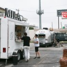 The Mila Coffee truck and the Bexar Goods Company streamline trailer are located in a parking lot at 2202 Broadway Street.