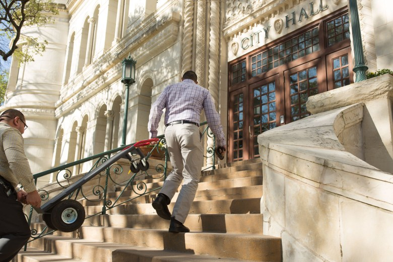 Citizens work together to carry a dolly up the steps of City Hall.