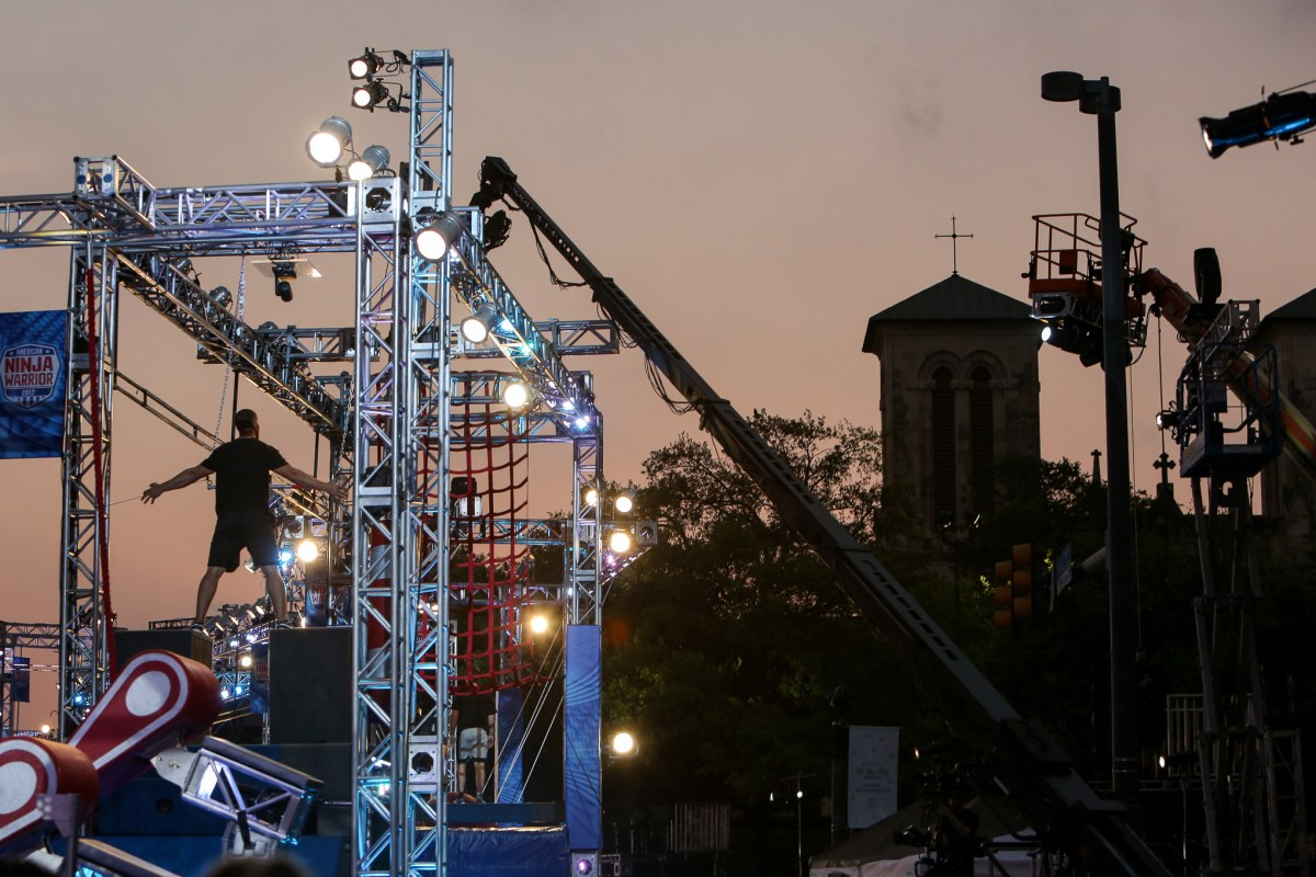An American Ninja Warrior trainer stands at the top of an obstacle overlooking San Fernando Cathedral.