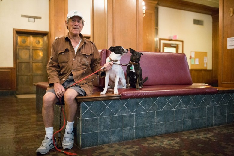 Robert Estrada sits with his dogs Bo-bo and Bubba in the lobby of the Aurora Apartments.