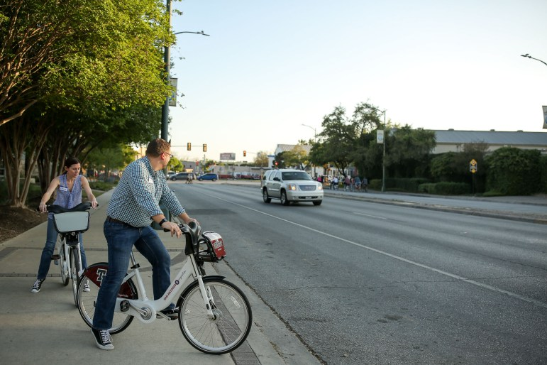 Attendees navigate across South Alamo Street with San Antonio BCycle.