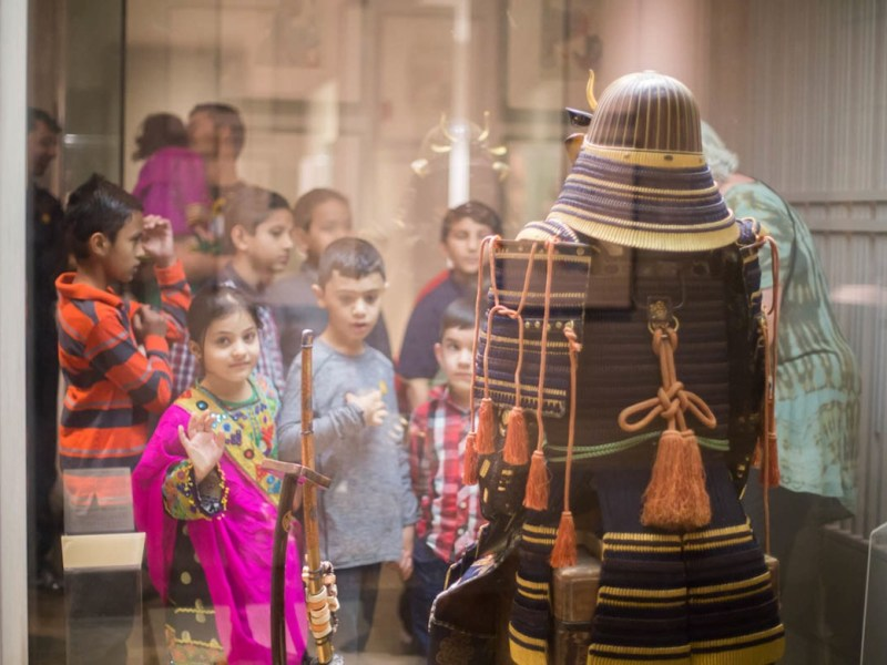 Children inspect ancient artifacts during Welcome Tour: It's Art in Any Language.