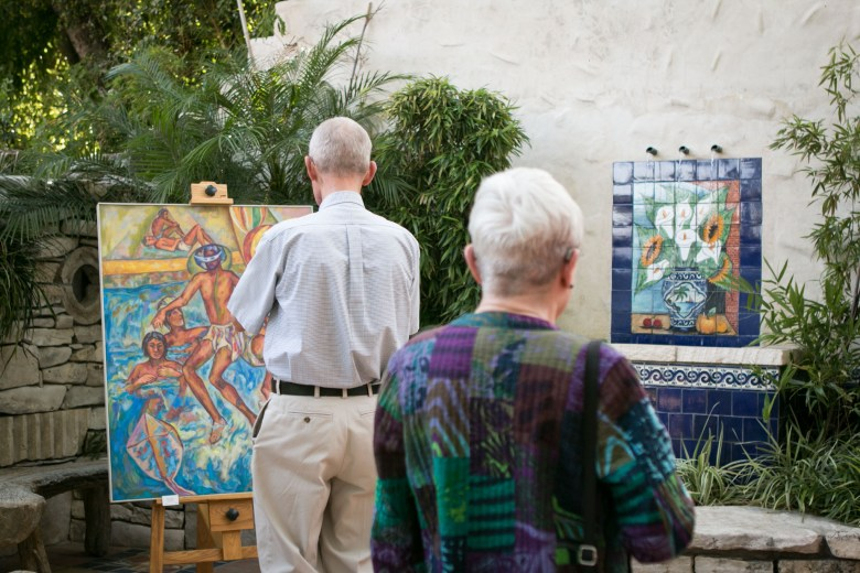 (From left) Maurice Fox and Beth Fox view paintings of the late José Guadiana that are displayed at the tribute to Alicia Guadiana.