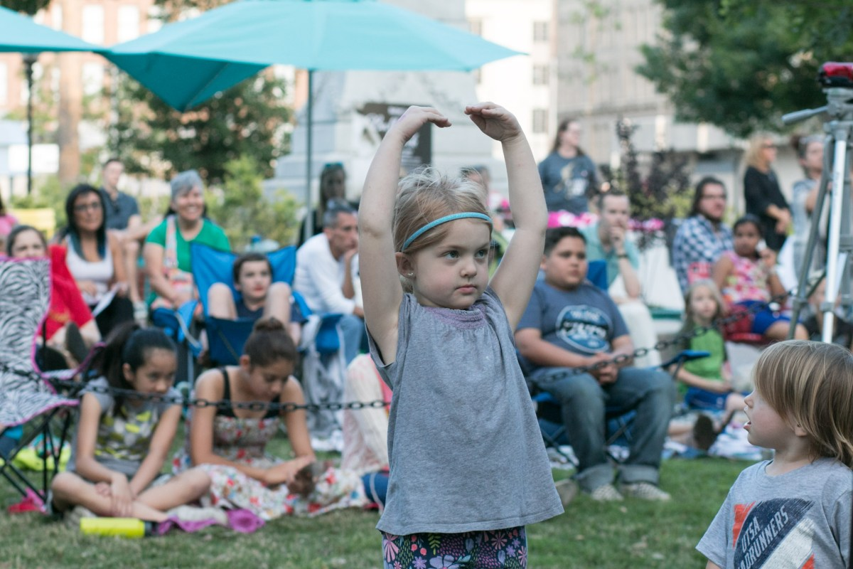 Ari, 5, practices ballet while watching a performance at Ballet in the Park.