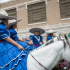Escaramuzas share a bottle of water during the Battle of Flowers Parade.