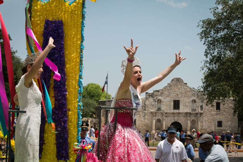 """Miss Fiesta San Antonio holds up her hands in a """"rock on"""" gesture at the Battle of the Flowers Parade."""