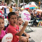 """(From left) Tatiana, 8, Patrick, 7, and Steven, 11, hold up their """"throw me a medal"""" signs during the Battle of Flowers parade."""