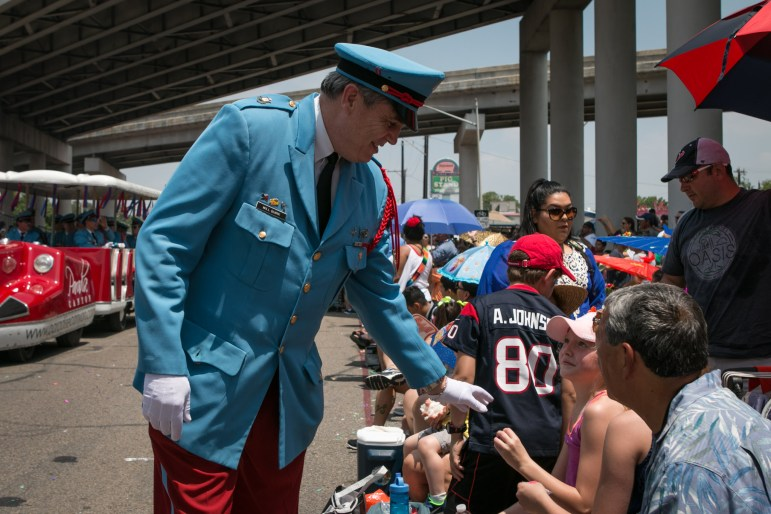 A Texas Cavalier hands a medal to a girl at the Battle of Flowers Parade.