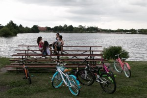 Friends and family park their bikes to eat popsicles at Woodlawn Lake Park in District 7.