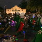 Sam Houston High School's marching band walks in front of the Alamo during the Fiesta Flambeau Parade.