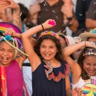 (From left) Emma, 10, Zoie, 10, and Valerie, 10, smash cascarones on their own heads during the Fiesta Flambeau Parade.