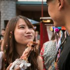 Kim Nguyen (left) smiles while eating a drumstick at NIOSA.