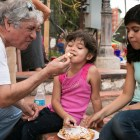 (From left) Mario Garcia, Charlotte, 4, and Cassandra, 11, share a funnel cake at NIOSA.