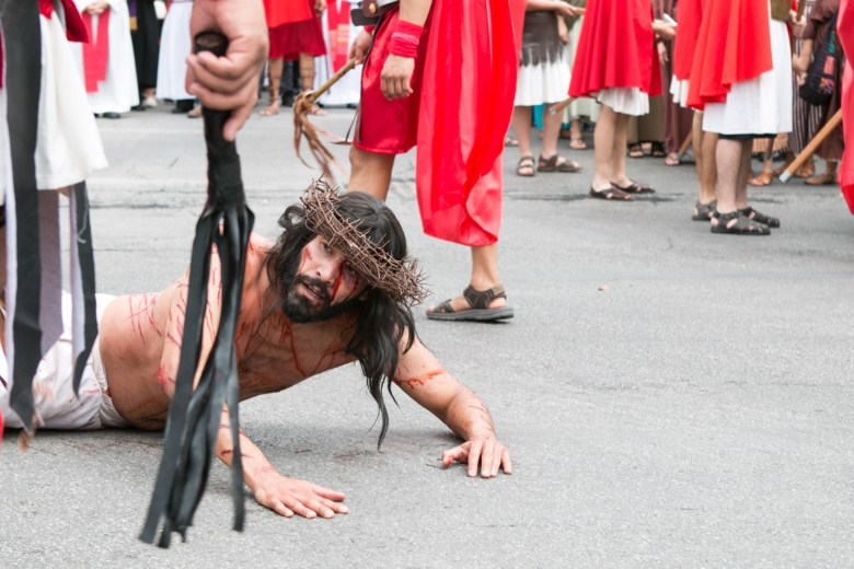 An actor portraying Jesus falls in pain at the Passion of Christ Procession.