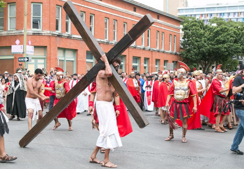 An actor portraying Jesus carries a large wooden cross at the Passion of Christ Procession.