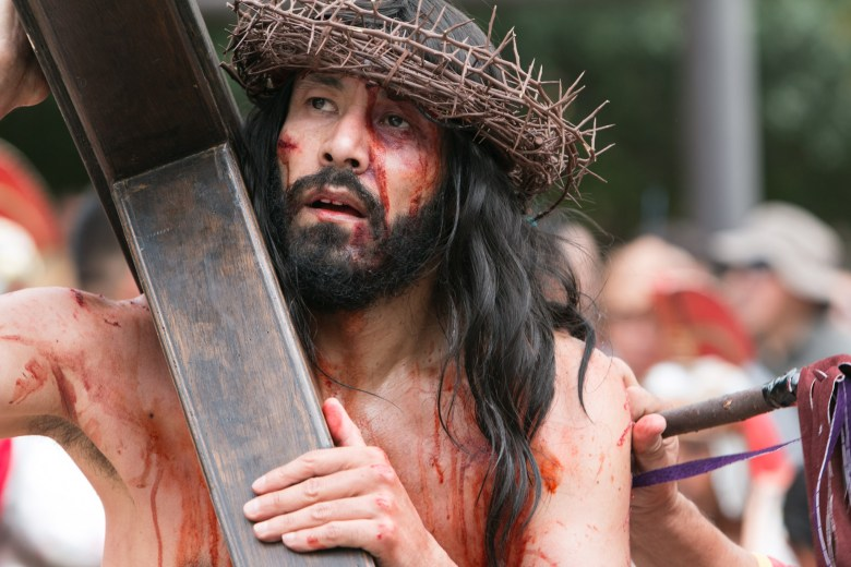 An actor portraying Jesus walks with a cross at the Passion of Christ Re-enactment at San Fernando Cathedral.