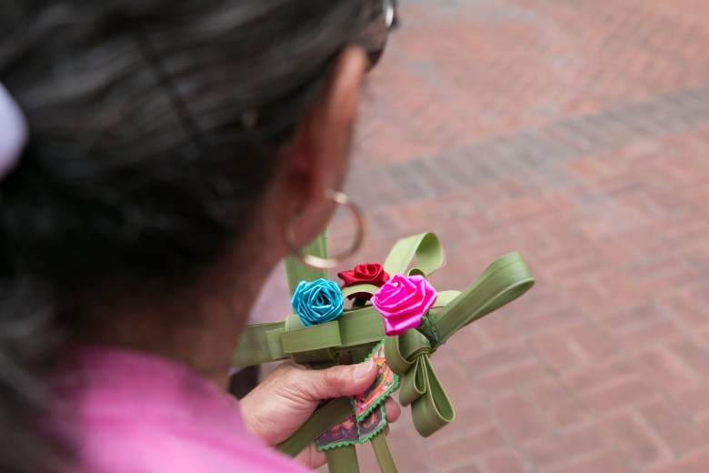 A woman holds a handmade cross at the Passion of Christ Procession.