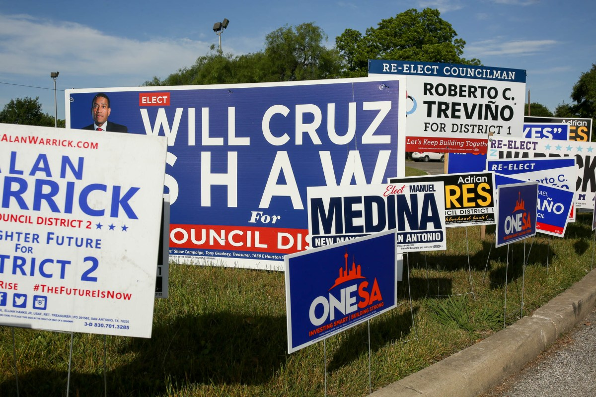 Candidate signs stack on the opening day of early voting in Bexar County at Lion's Field Park.