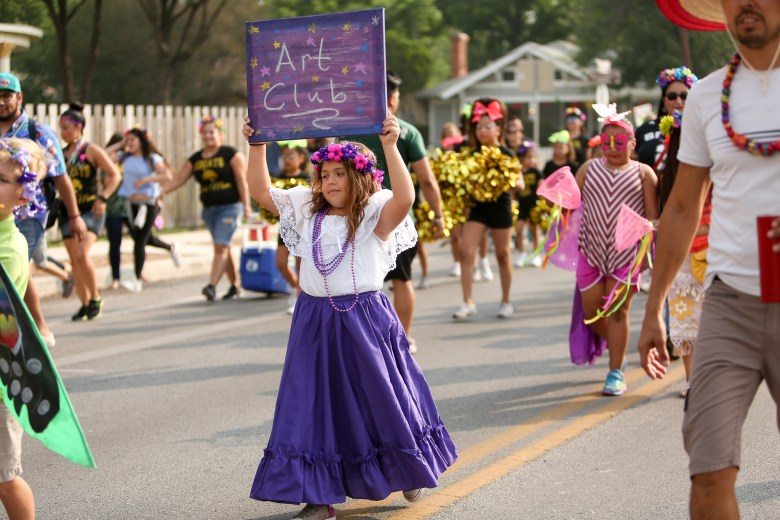 A child holds up a sign as they start along the parade route.