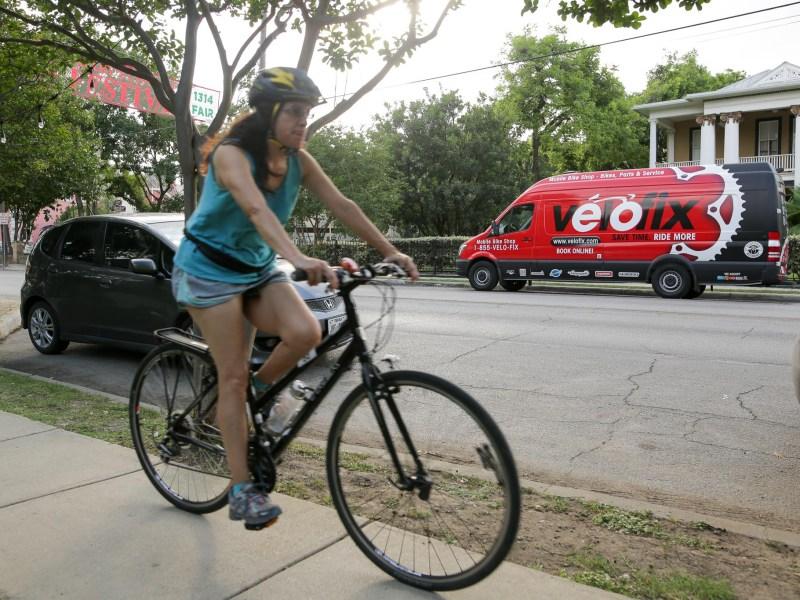 Cyclists pass Velofix on South Alamo Street on Sunday evening.