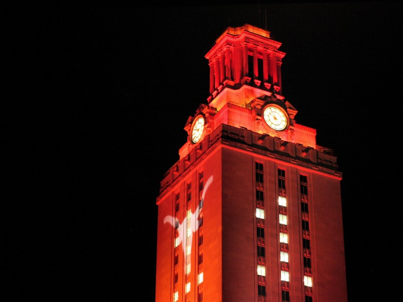 The University of Texas-Austin Tower is lit orange during graduation in 2013.