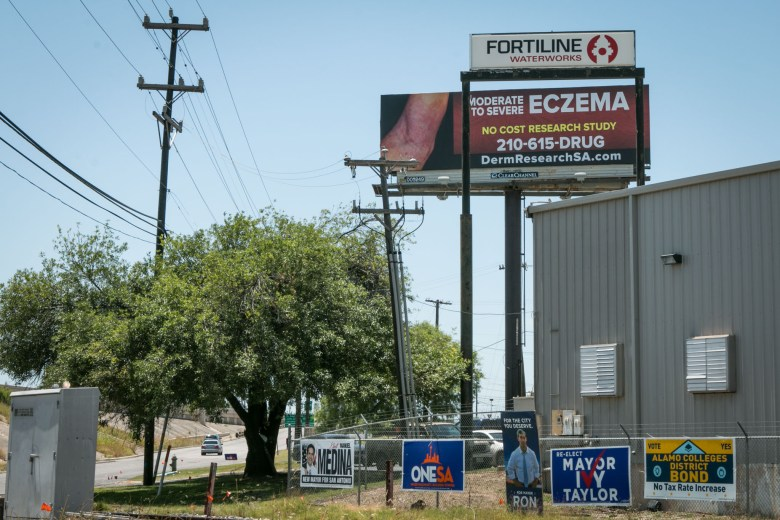 A billboard for an eczema research study lines N Panam Expy.