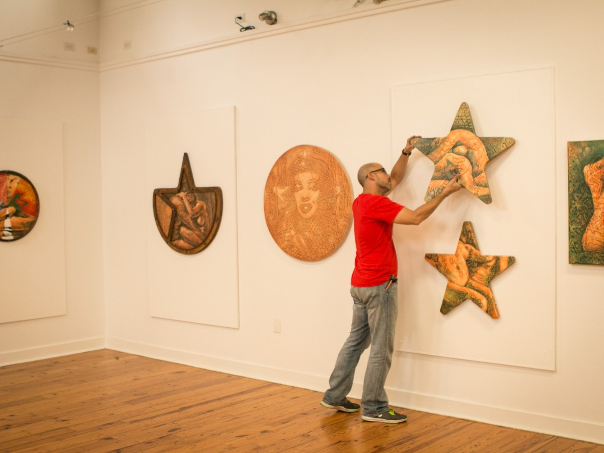Artist Adrian Rumbaut mounts a work onto the wall before the Cuerpo Cubano / Cuban Body show at Bihl Haus Arts.