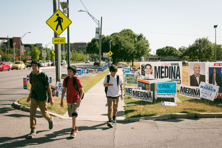 Boys walk past campaign signs at the early voting site at Lions Field.
