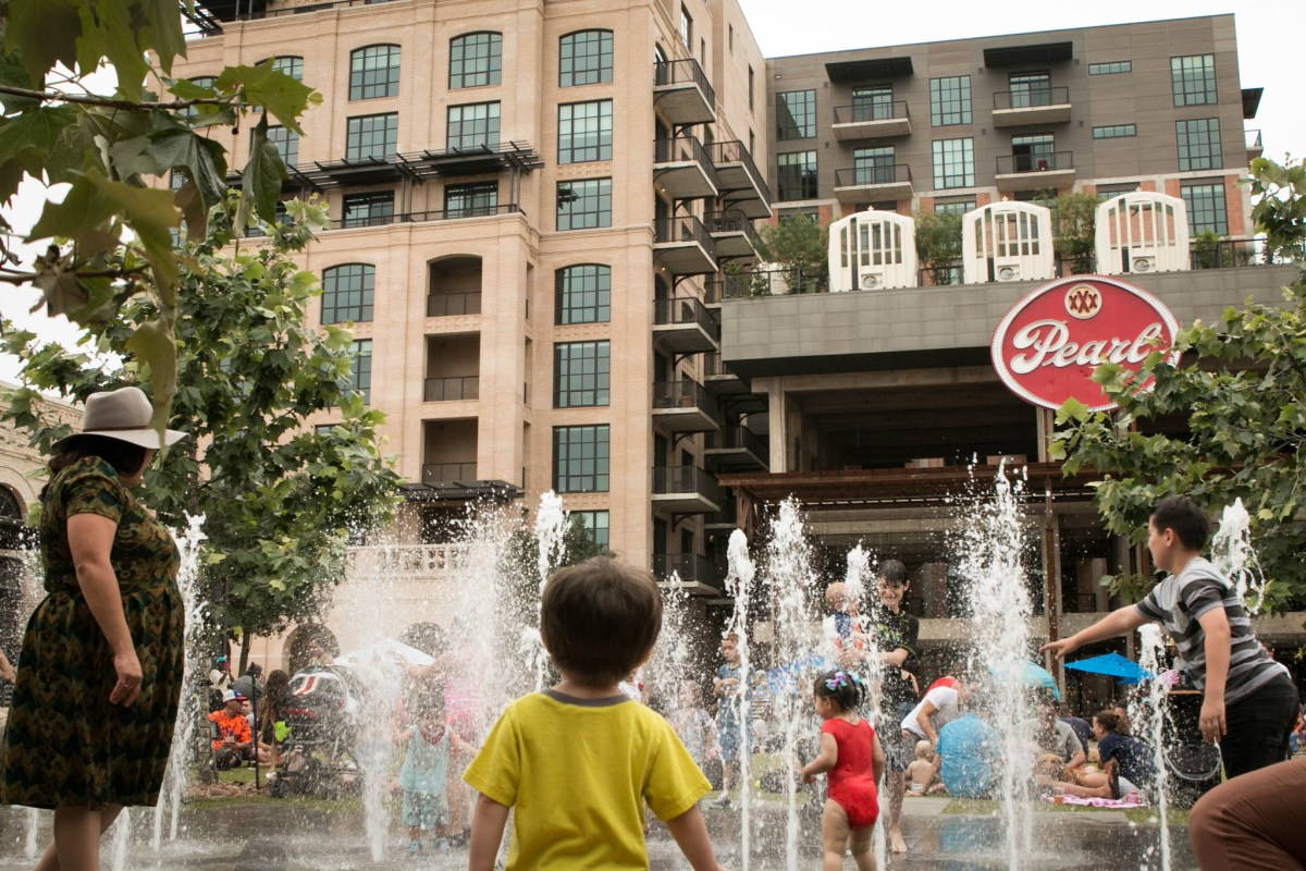 Children play in the fountain outside of the new Cellars apartments at the Pearl.