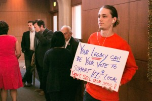 Alek Harmeyer stands at the back of City Council chambers with a sign in support of a local company's bid for the river barge contract.
