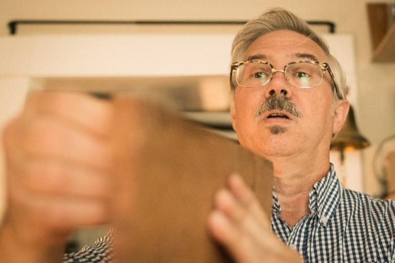 Scott Albert examines the edge of a piece of wood.