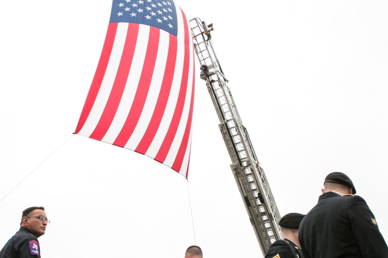 An American flag hangs from two firetrucks in front of Community Bible Church.