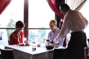 Server Rey Martinez presents food to customers Judy Weedon (left) and Jim Weedon.
