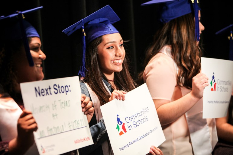 South San Antonio High School student Samantha Magna smiles as she holds a a sign promoting Communities In Schools (CIS) at the surprise graduation celebration.
