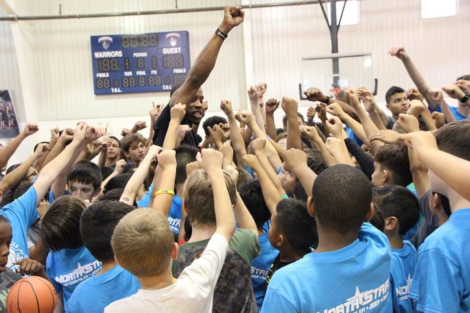 Antonio Daniels and camp participants raise their hands together in preparation for the final game of the Antonio Daniels Basketball Camp.
