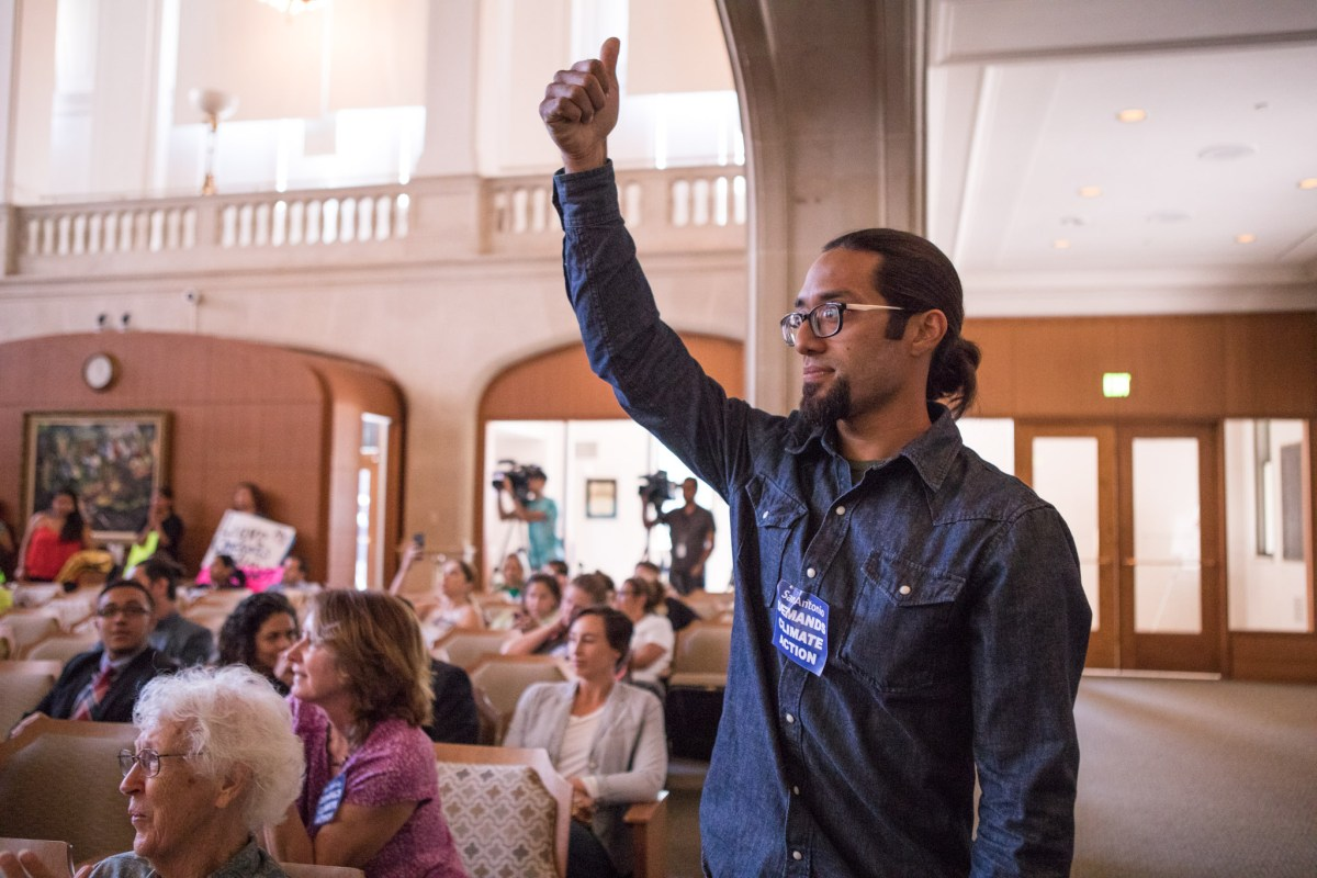 Ruben Martinez puts his thumb up after the Paris Agreement motion is passed in City Council Chambers.