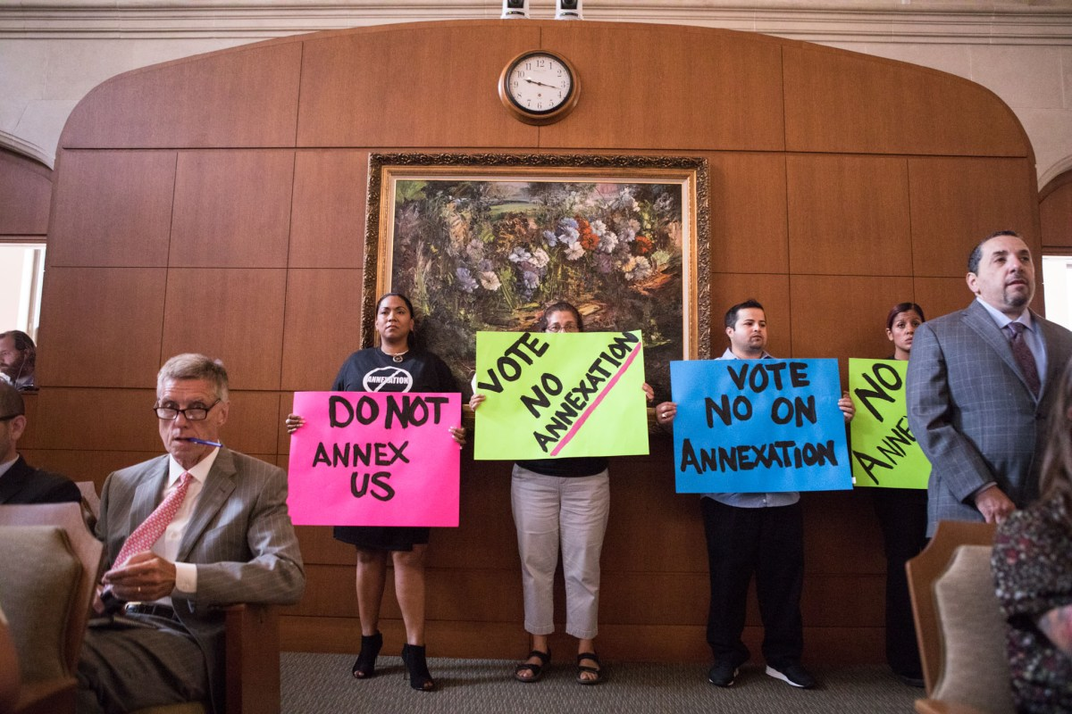 Citizens hold up signs in City Council Chambers.