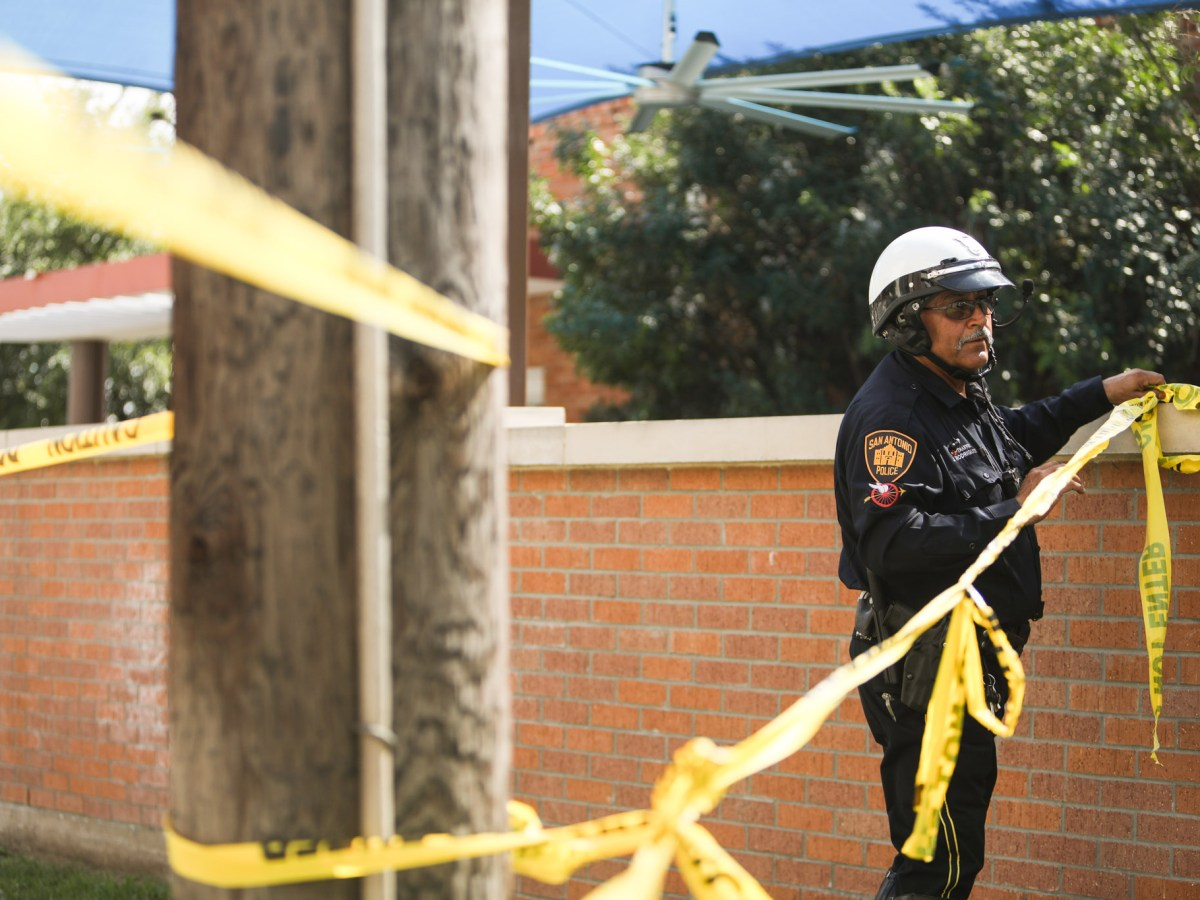 A police officer ties up crime scene tape on Evergreen Street and Howard Street.