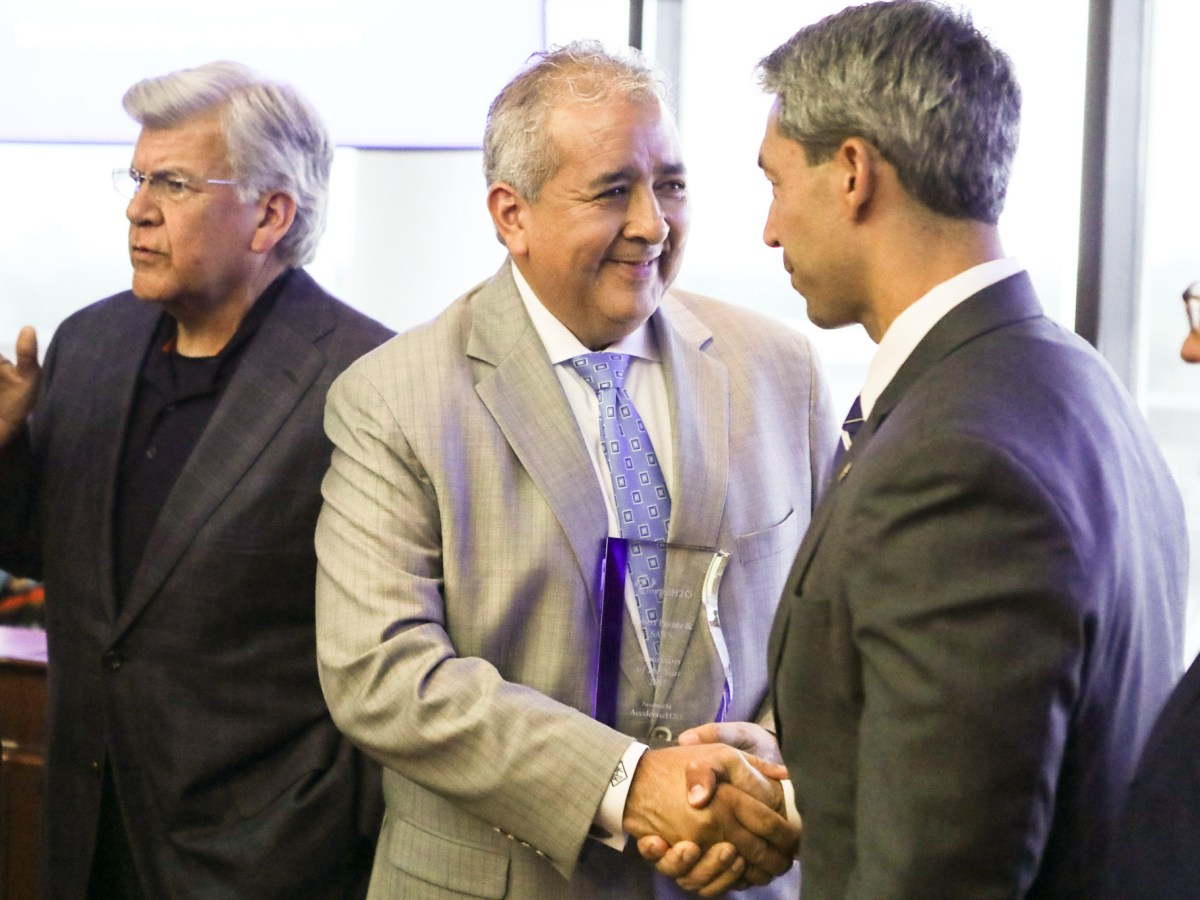 """San Antonio Water System President & CEO Robert Puente shakes the hand of Mayor Ron Nirenberg after receiving the """"Innovator of the Year"""" award."""
