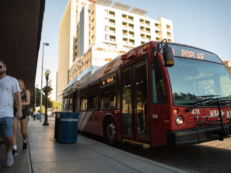 A VIA Metropolitan Transit bus stops at the corner of Commerce Street and Soledad Street.