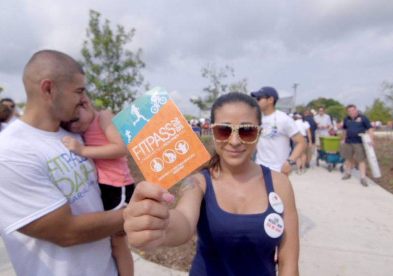 A Fit Pass participant shows off her Fit Pass passport at the 2016 kickoff event a Pearsall Park.