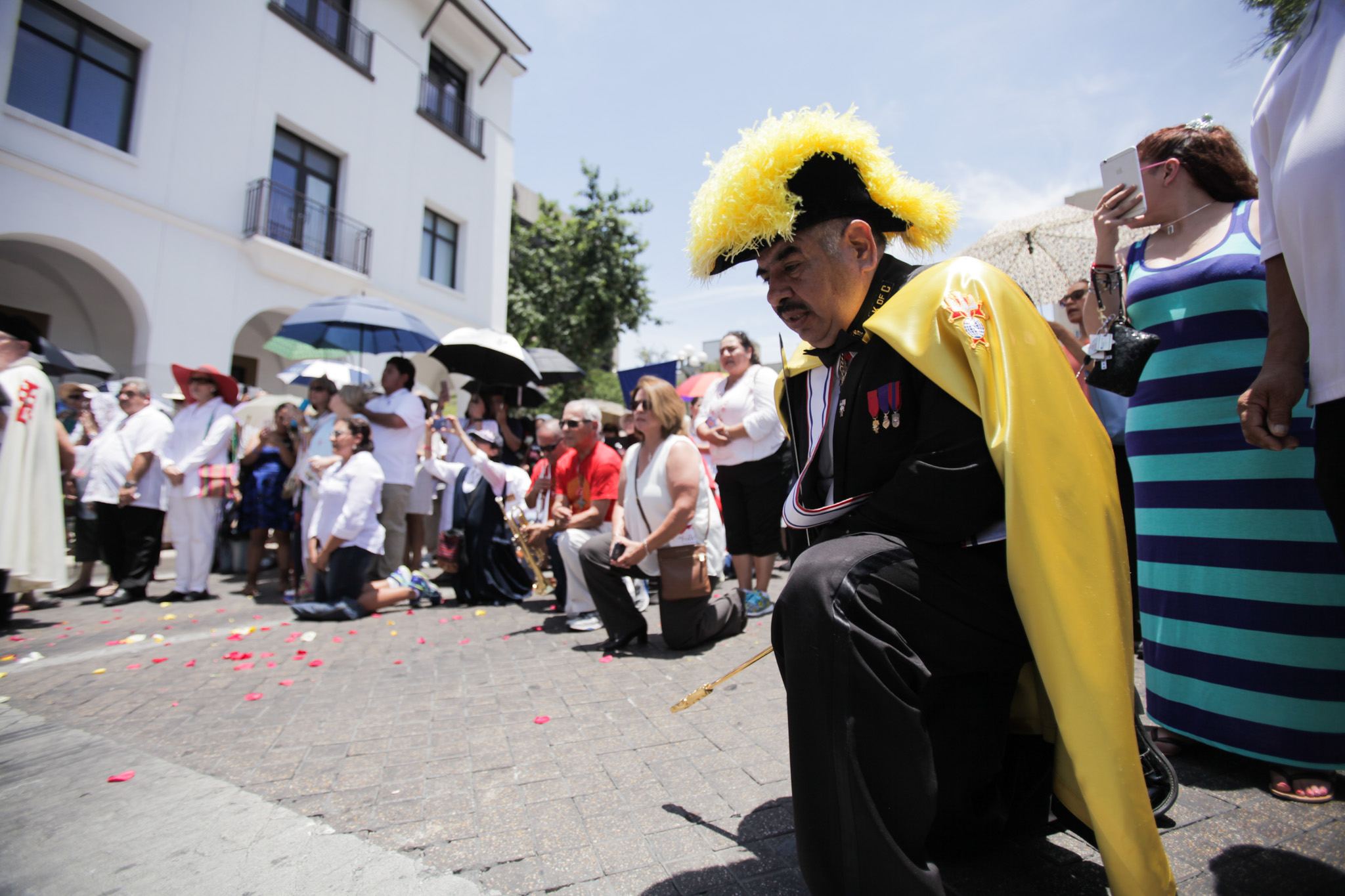 A Knight of Colombus kneels in prayer during the Feast of Corpus Christi Procession held in downtown San Antonio.